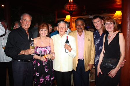Peter Malhotra presents a bottle of wine to Archie. From left: Dr. Iain Corness, Elfi Seitz, Archie Dunlop, Peter Malhotra along with Arthur & Alisa.