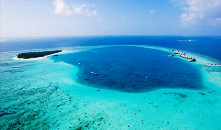 A bird's eye view shows the South Nilandhe Atoll and the Angsana Velavaru resort.