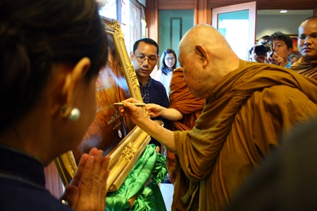 Luangphor Viriyang autographs a portrait of himself on arrival at the Diana Garden Resort.