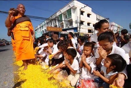 "Citizens sprinkle marigold petals on the rose way during the ""Dhammachai Dhutanga"" pilgrimage. (Photo from www.dmc.tv)"