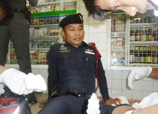 Emergency workers tend to Sgt. Ruangchai Prachaipoom's gunshot wound to his leg.