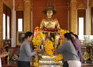 At the King Taksin statue, people present fruit, pig heads, ducks and chicken, while others gild the statue with gold leaf.