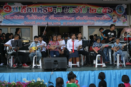 Pattaya schoolchildren give a rousing ukulele performance while their friends stand on the sides providing encouragement.