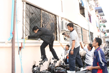 Investigators inspect the scene of a shotgun blast into Pattaya's new police chief's residence.