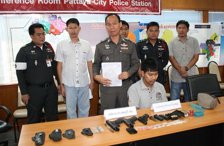 Chonburi Police Station Commander Maj. Gen. Khatcha Thatsart (standing center) announces results of the recent crackdown on crime.