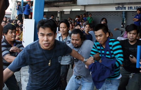 Initially defiant when arriving at the scene, confessed murderer Thiwanont Bunruang (striped shirt, right) had to run for his life when the crowd turned on him, despite undercover cops doing their best to protect him.