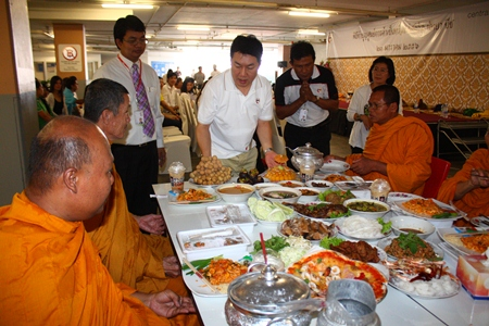 General Manager Saran Tantijamnaj (center) serves lunch to the monks during Central's anniversary merit making.