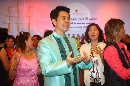 Chonburi MP Poramet Ngampichet, wearing a handsome Thai outfit that he modeled in the fashion show, dances with guests.