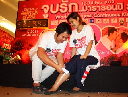 Krittirat Chaikhum applies muscle balm to Kanokwan Aajkhidkarn's legs after 53 hours 56 minutes and 38 seconds of continuous kissing, beating the previous record but falling nearly 5 hours short of winning this year.