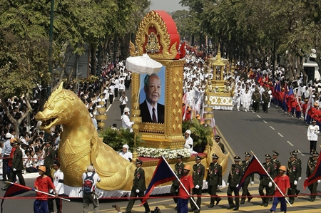 The chariot carrying the portrait of late former King Norodom Sihanouk leads his royal funeral procession Friday, Feb. 1, 2013, in Phnom Penh, Cambodia. Thousands of mourners accompanied a gilded chariot carrying the body of former King Sihanouk - the dominant figure of modern Cambodia - in a funeral procession Friday to a cremation ground next to the palace where he was crowned more than 70 years ago. (AP Photo/Heng Sinith)