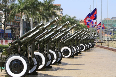 Cambodian flags fly at half-mast as cannons are placed for gun salutes during the cremation of former King Norodom Sihanouk near the Royal Palace in Phnom Penh, Monday, Feb. 4. (AP Photo/Heng Sinith)