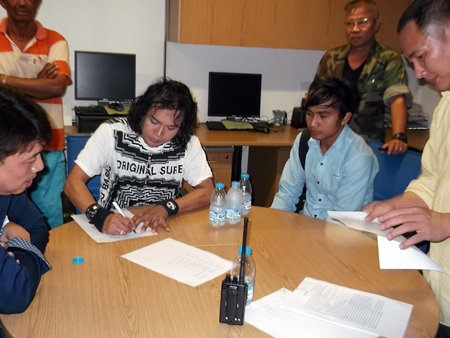 Performer Montchai Raksachart signs the complaint filed by Prasith Prasertkittikul of industry giant GMM Music Publishing International Co.