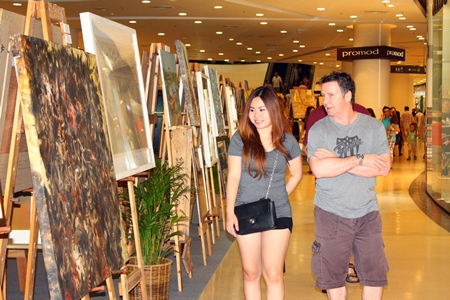 Tourists admire paintings at the 3rd art exhibition in honor of HM the King in Central Festival Pattaya Beach.