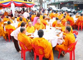 Monks from Chaiyamongkol Phra Aaramluang Temple are seated for lunch at South Pattaya's old pier, for a merit making ceremony organized by the Sawang Boriboon Thammasathan Foundation.