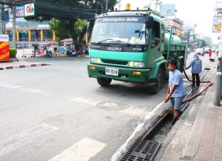City workers clean out the drains along Second Road in North Pattaya.