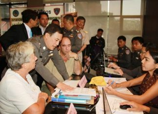 Royal Thai Police advisor Lt. Col. Wuthi Liptapanlop leans in to talk with foreign guests at the new consumer protection office inside city hall.