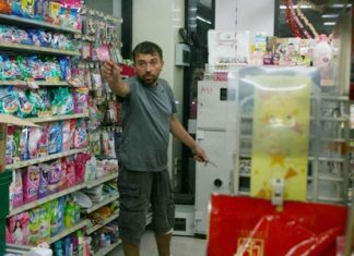 Yuri Gubenko, allegedly upset over the loss of his girlfriend, threatens police with a pair of knives inside an East Pattaya 7-Eleven.