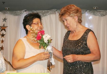 """Founding member Somthavin """"Tiew"""" Suphamongkon (left) receives flowers from Ann Winfield."""
