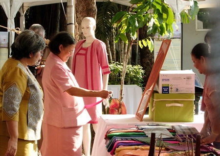 HRH Princess Maha Chakri Sirindhorn inspects some of the Mudmee silk on display at the celebration of the 150th anniversary of Queen Savang Vadhana's birth.