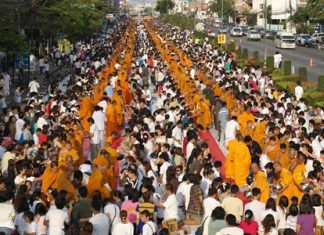 The southbound lane on Sukhumvit Road in Rayong was turned into a sea of orange and white as residents presented alms to 2600 monks to celebrate Jayanti.