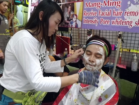 "Laddawan Saeyuang works her ""mang ming"" hair removal system on a customer."