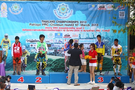 Lt. Gen. Phadungsak Klansanoh, vice president of Thai Cyclist Association under the royal patronage, presents medals to winning cyclists in the U 14 female category.