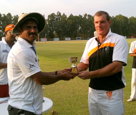 Simon Phillbrook (right) presents a trophy to the captain of the RAW Cricket Club following their match at Thai Polo Club, Saturday, March 2.