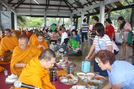 Sattahip residents present alms to local monks as part of the region's official Songkran commemoration.