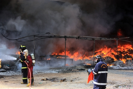 Fire police battle the inferno at the Master Glove Industries Co. plant in Pluakdaeng.