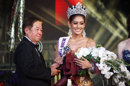 Sutham Phanthusak, Managing Director of Tiffany's Show Pattaya Co., Ltd., presents the championship trophy to Netnapada Kanlayanon, winner of Miss Tiffany's Universe 2013.