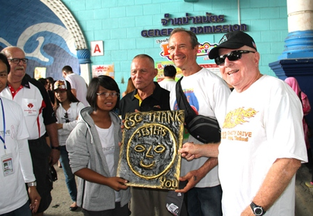 """(L to R) Nam Wan presents a plaque of appreciation she made to Bill Freeman, Lewis """"Woody"""" Underwood, and Earl Kershaw from Jesters Care for Kids."""