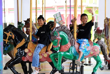 Youngsters enjoy riding the horses on the merry-go-round.