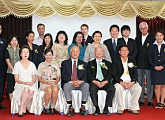 University president Dr. Viphandh Roengpithya (center) sits for a commemorative photo with students, teachers and local officials during the opening ceremony.