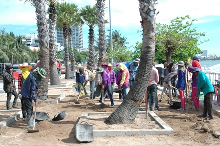 Laborers, some shown here improving the diminishing beach landscape for the May Day celebration, say 300 baht a day is still not enough for them to make ends meet in today's ever changing economy.