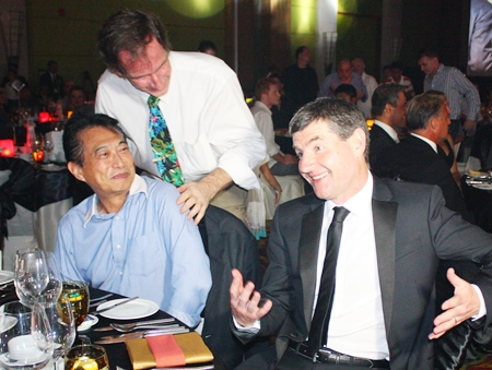 Dennis Irwin (right) jokes with guests at the dinner table.