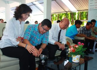 (L to R) Jidapa Suwattaporn, member of Pattaya city council, and deputy mayors Verawat Khakhay and Wattana Chantanawaranon pour holy water while attending the religious ceremony carried out by monks on the 62nd anniversary of Pattaya School No. 5.
