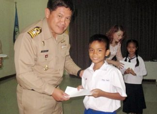 Royal Thai Navy's 2nd Anti-Aircraft Artillery Regiment commander, Capt. Wirat Somjit presents one of the 2,000 stipends to a grateful student.
