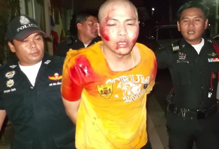 Police bring in Kritpol Khruthern for shooting a motorcyclist during a road rage crime that spilled over into a Pattaya neighborhood.