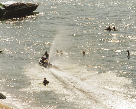 1995 - Safe to swim in Pattaya? Swimmers play in shallow water amongst speed boats and speeding water scooters - in the area where a swimmer was struck and killed.