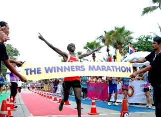 Joseph Kariuki of Kenya celebrates with arms aloft as he crosses the finish line to win the 2013 King's Cup Pattaya Marathon, Sunday, July 21. African athletes filled the top seven positions in the men's division and the women's race was also won by a Kenyan athlete, but the event was more a celebration of spirit and fortitude as runners of all ages and nationalities took to Pattaya's streets to face their own personal sporting challenges. (PM Photo/Phasakorn Channgam)