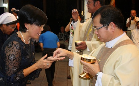 Father Michael Picharn presents communion to Toy, Father Ray's 'right hand woman'.