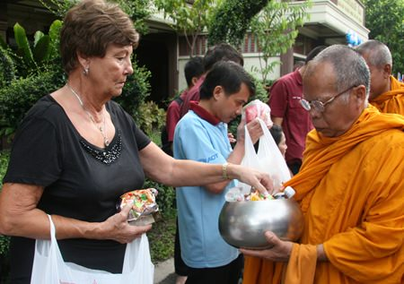 Sharron Purtell offers food to the monks.