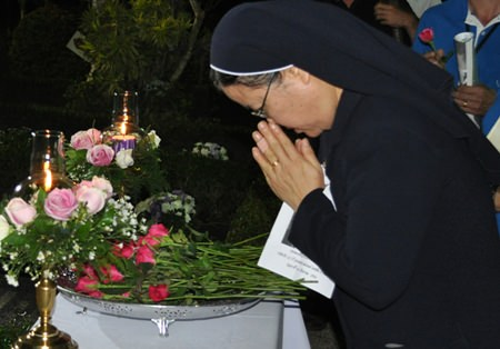 Sister Supatra pays her respects to Father Ray.