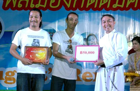 "Amateur musicians Nopawad Samanrak (left), and Manaswee Samanrak (center) accept the winning award for writing the song, ""Father Ray in our Heart""."