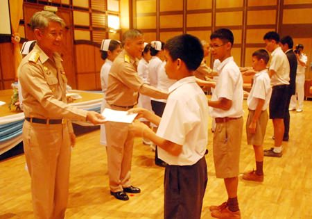 Queen Sirikit Naval Medical Center Deputy Director Vice Adm. Chumpol Thienchai hands out scholarships to children of government employees and navy personnel.