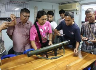 Officials and media inspect a shoulder fired anti-tank weapon found in the middle of a quiet Sattahip street.