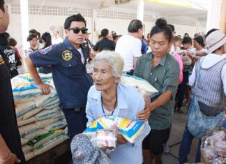 Members of the Sawang Rojthummasathan Foundation donate rice and dried food to 3,999 Sattahip-area residents.