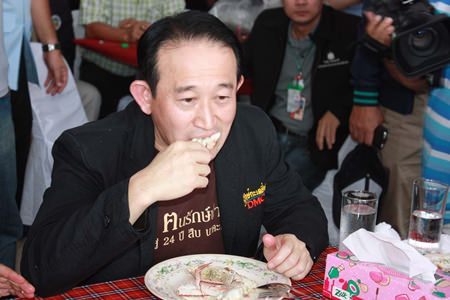 Pornthep Siriwanarangsan, director-general of the Disease Control Department, indulges in the local crab whilst trying to convince others that Koh Samet seafood is safe to eat.
