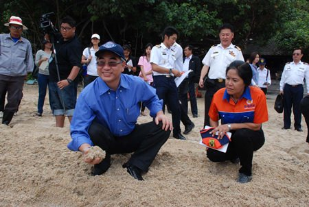 Natural Resources and the Environment Minister Vichet Kasemthongsri smiles as he checks the sand for a photo op on Ao Phrao beach.