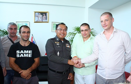 Capt. Samruay Saman (center), deputy suppression inspector for Chonburi Immigration, shakes hands with Illia Miasnikov (2nd right), Security Advisor at the Russian Convenience Center, as other Russians look on.